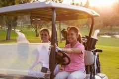 Jogadores de golfe fêmeas que conduzem o carrinho ao longo do fairway do campo de golfe imagem de stock royalty free