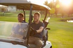 Jogadores de golfe masculinos que conduzem o carrinho ao longo do fairway do campo de golfe fotos de stock