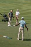 Jogadores de golfe multi-étnicos que falam durante o jogo no passo verde no dia Fotos de Stock