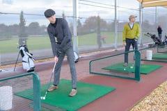 Jogadores de golfe no treinamento dentro imagens de stock