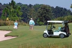 Jogadores de golfe no verde com carro Fotografia de Stock
