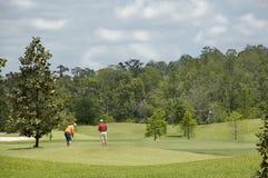 Jogadores de golfe no verde do golfe de Florida imagem de stock