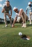 Jogadores de golfe profissional que olham a bola perto do furo Fotos de Stock Royalty Free