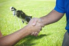 Jogadores de golfe que agitam as mãos Fotografia de Stock Royalty Free