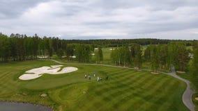 Jogadores de golfe que batem o tiro de golfe com o clube no curso quando nas férias de verão, aéreas foto de stock
