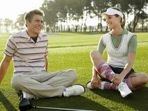 Jogadores de golfe que sentam-se no campo de golfe Fotografia de Stock