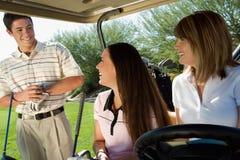 Jogadores de golfe que sentam-se no carro de golfe Foto de Stock Royalty Free