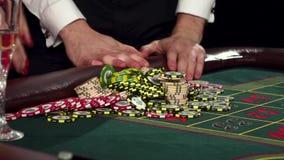 Jogadores de pôquer com as microplaquetas na tabela verde do casino preto filme