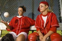 Jogadores de softball que sentam-se no banco foto de stock