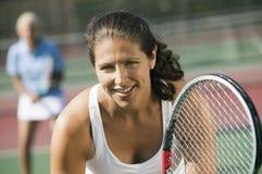 Jogadores de tênis dos dobros da fêmea que esperam o foco do saque no fim do primeiro plano acima foto de stock