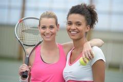 Jogadores de tênis fêmeas que jogam dobros no campo de tênis fotos de stock royalty free