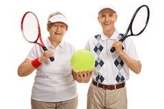 Jogadores de tênis idosos felizes que guardam uma bola de tênis grande imagem de stock