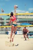 Jogadores de voleibol da praia das mulheres A mulher que salta fazendo o ponto Imagem de Stock Royalty Free