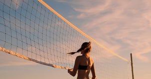 Jogadores de voleibol fêmeas novos para passar e cravar a bola sobre a rede em uma noite ensolarada do verão Meninas caucasianos  filme