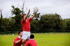 Jogadores do rugby que saltam para a linha para fora Fotografia de Stock Royalty Free