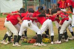 Jogadores que discutem e que cheering acima em um fósforo do basebol Fotos de Stock