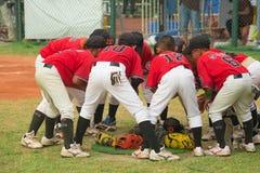 Jogadores que discutem e que cheering acima em um fósforo do basebol Foto de Stock