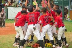 Jogadores que discutem e que cheering acima em um fósforo do basebol Imagens de Stock