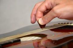 Jogando a guitarra acústica com picareta Imagens de Stock Royalty Free