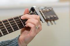 Jogando a guitarra com capo - close up imagem de stock