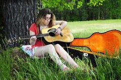 Jogando a guitarra nas madeiras fotografia de stock royalty free