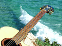 Jogando a guitarra que olha o mar Imagens de Stock