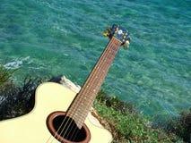 Jogando a guitarra que olha o mar Fotos de Stock Royalty Free