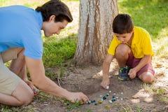 Jogando mármores com meu paizinho Foto de Stock Royalty Free