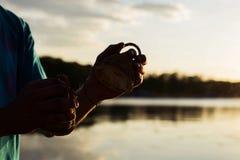 Jogando maracas ou caxixi de um instrumento musical no céu do fundo no por do sol foto de stock royalty free