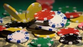 Jogando no casino, lotes das microplaquetas coloridas que caem em cima do dinheiro na tabela verde vídeos de arquivo