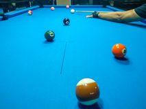 Jogando o bilhar - um tiro de um homem que joga o bilhar em uma mesa de bilhar azul foto de stock