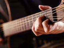 Jogando o close up da guitarra acústica Foto de Stock Royalty Free