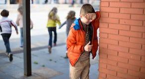 Jogando o couro cru - e - busca olhos fechados do menino suas mãos que estão no bri imagens de stock royalty free
