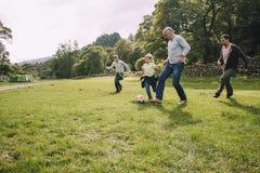 Jogando o futebol com vovô foto de stock royalty free