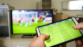 Jogando o futebol em uma tevê com smartphone fotografia de stock