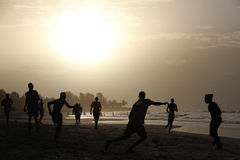 Jogando o futebol na praia gambiana Imagens de Stock Royalty Free