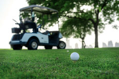 Jogando o golfe e um carrinho de golfe A bola de golfe está no T para um golfe Fotos de Stock