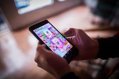 Jogando o jogo da saga do esmagamento dos doces imagens de stock royalty free