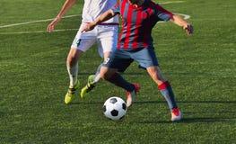 Jogando o jogo de futebol do futebol no campo de esportes Fotografia de Stock Royalty Free