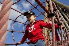 Jogando o menino na ponte de corda Fotos de Stock Royalty Free