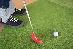 Jogando o mini golfe com putter vermelho Imagem de Stock