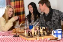 Jogando o riso dos amigos do chalé do inverno da xadrez Fotografia de Stock Royalty Free