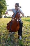 Jogando o violoncelo no prado fotos de stock royalty free