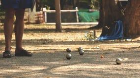 Jogando Petanque no parque - bolas de metal e bola de madeira alaranjada na jarda da rocha com um homem que está no Sun fotos de stock royalty free