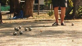 Jogando Petanque no parque - bolas de metal e bola de madeira alaranjada na jarda da rocha com um homem que está no Sun fotografia de stock royalty free