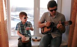 Jogando um instrumento musical nos óculos de sol O paizinho está jogando a guitarra e o filho está jogando o cilindro que senta-s fotos de stock royalty free