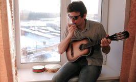 Jogando um instrumento musical O homem está jogando o órgão de boca que senta-se na soleira fotos de stock