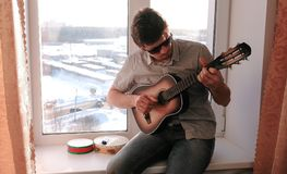 Jogando um instrumento musical O homem está jogando a guitarra que senta-se na soleira fotos de stock royalty free