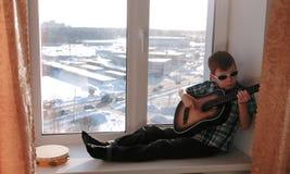 Jogando um instrumento musical O menino nos óculos de sol joga a guitarra que senta-se na soleira imagens de stock