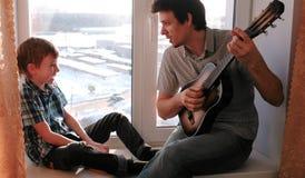 Jogando um instrumento musical O paizinho está jogando a guitarra e o filho está jogando o pandeiro que senta-se na soleira imagem de stock